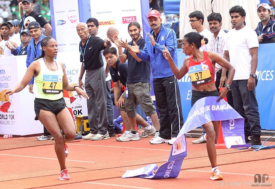 Dire Tune of Ethiopia gestures to fellow national Merima Mohammed as she crosses the finishing line during a close finish at Shree Kanteerava Stadium to win the Gold in the Elite Womens category of Bangalore World 10k race. Sunday, 5th June 2011. - (Nishant Ratnakar/DNA)
